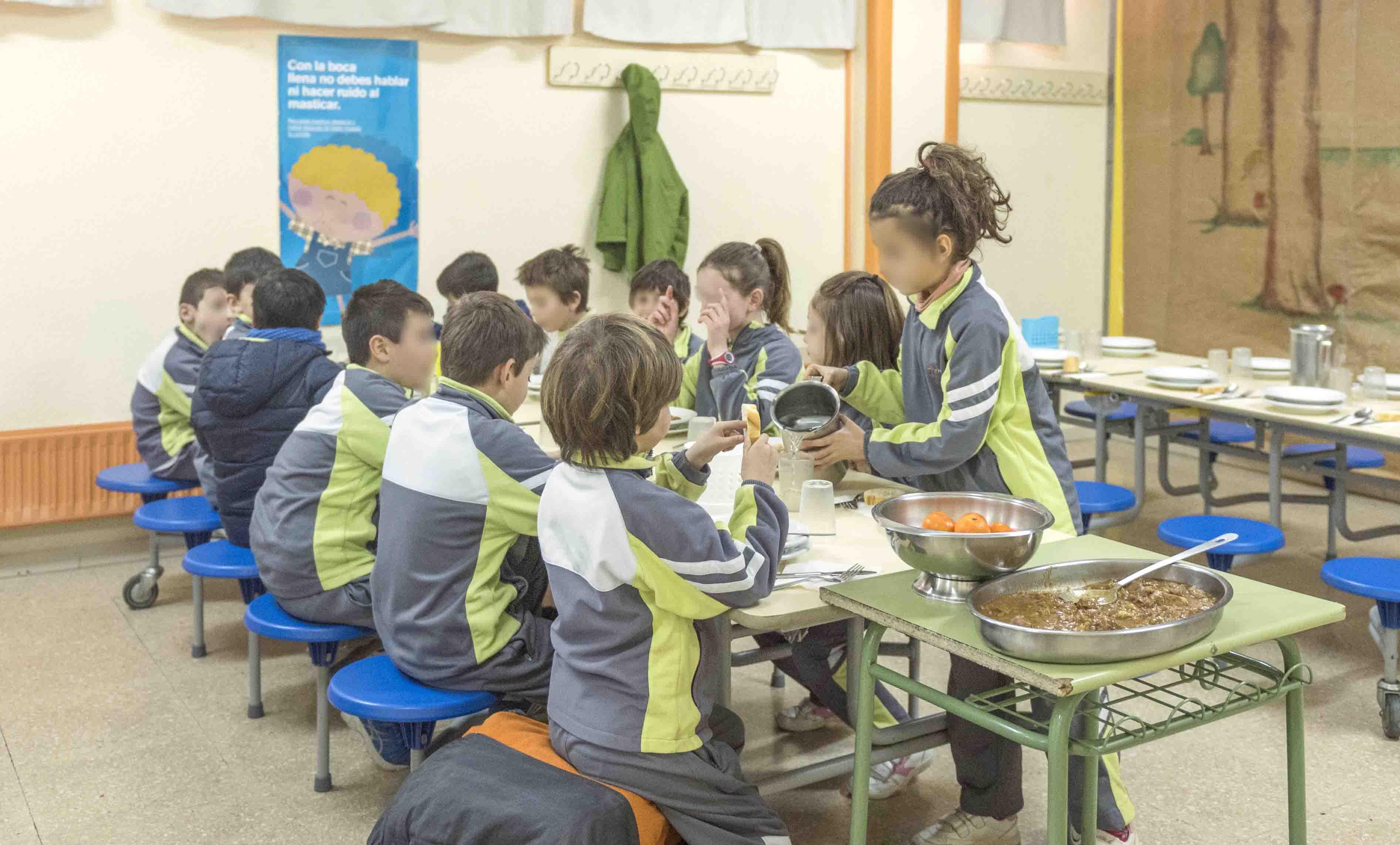 Niños comiendo en Brotmadrid. Se aprecia una mesa con 12 niños. En primer plano una niña se sirve agua de una jarra. Se aprecian bandejas con la comida del día.