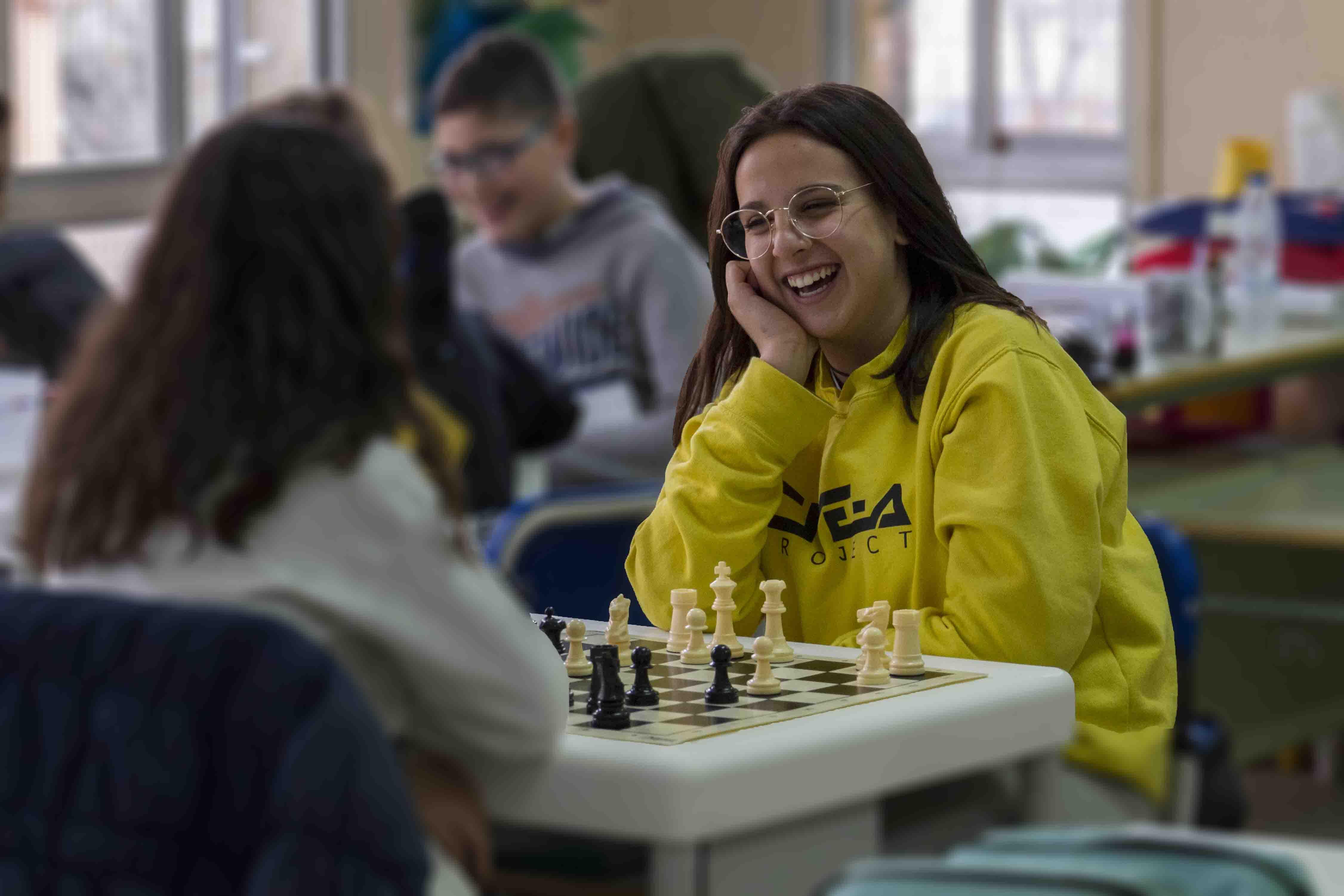 Clase de ajedrez. En primer plano se muestra a una chica sonriente, vestida con sudadera de amarillo con la mano apoyada en la cara mirando a su compañera.